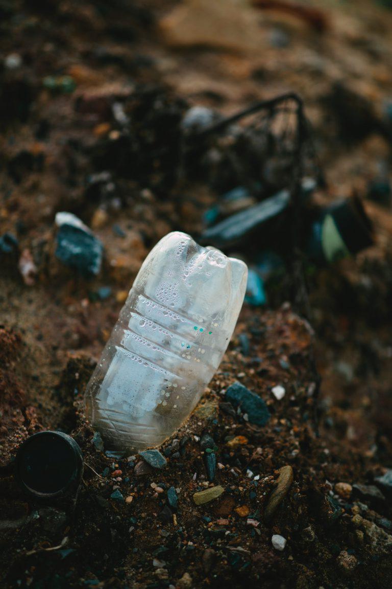 white plastic bottle on brown soil